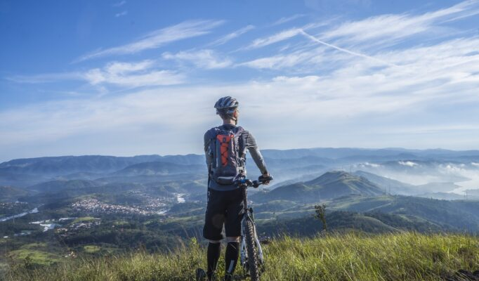 biker-holding-mountain-bike-on-top-of-mountain-with-green-161172
