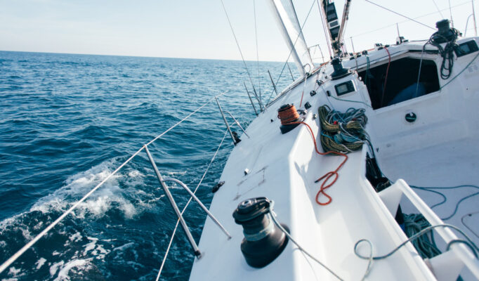 deck-professional-sailboat-racing-yacht-during-competition-sunny-windy-summer-day-moving-fast-through-waves-water-with-spinnaker-up