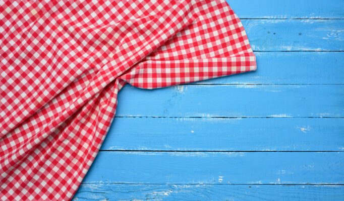 folded-red-white-cotton-kitchen-napkin-wooden-blue-background-top-view-copy-space