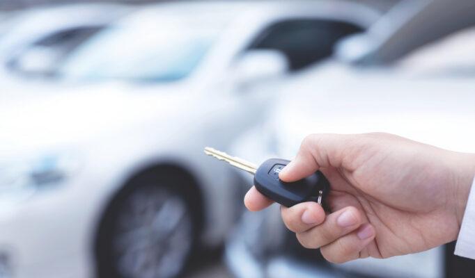 man-holding-car-key-presses-it-parking